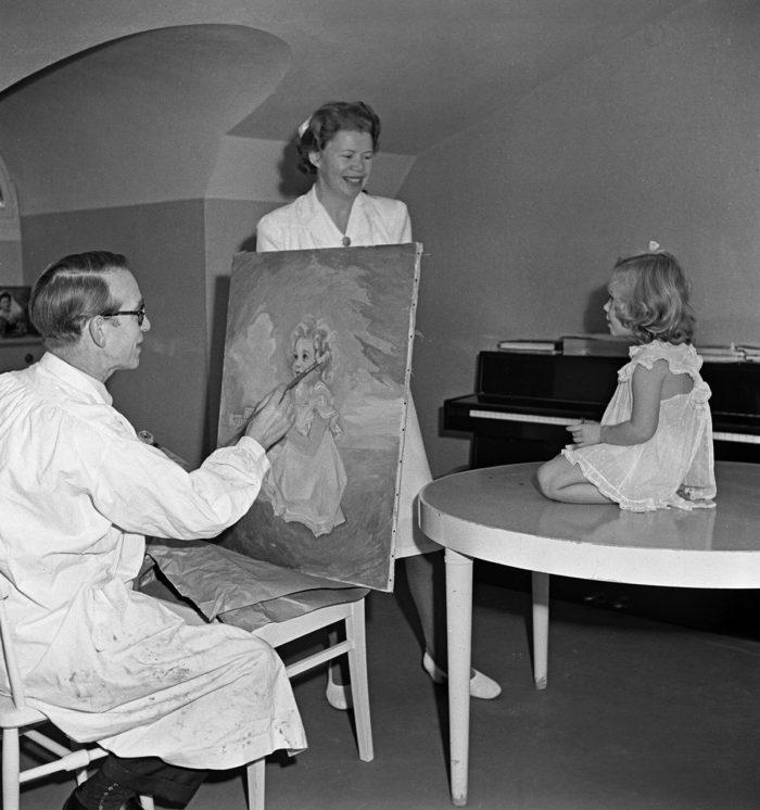 """Konstnären Einar Nerman målar av prinsessan Christinas porträtt på Haga slott. Med på bilden är också barnsköterskan Ingrid """"Nenne"""" Björnberg."""