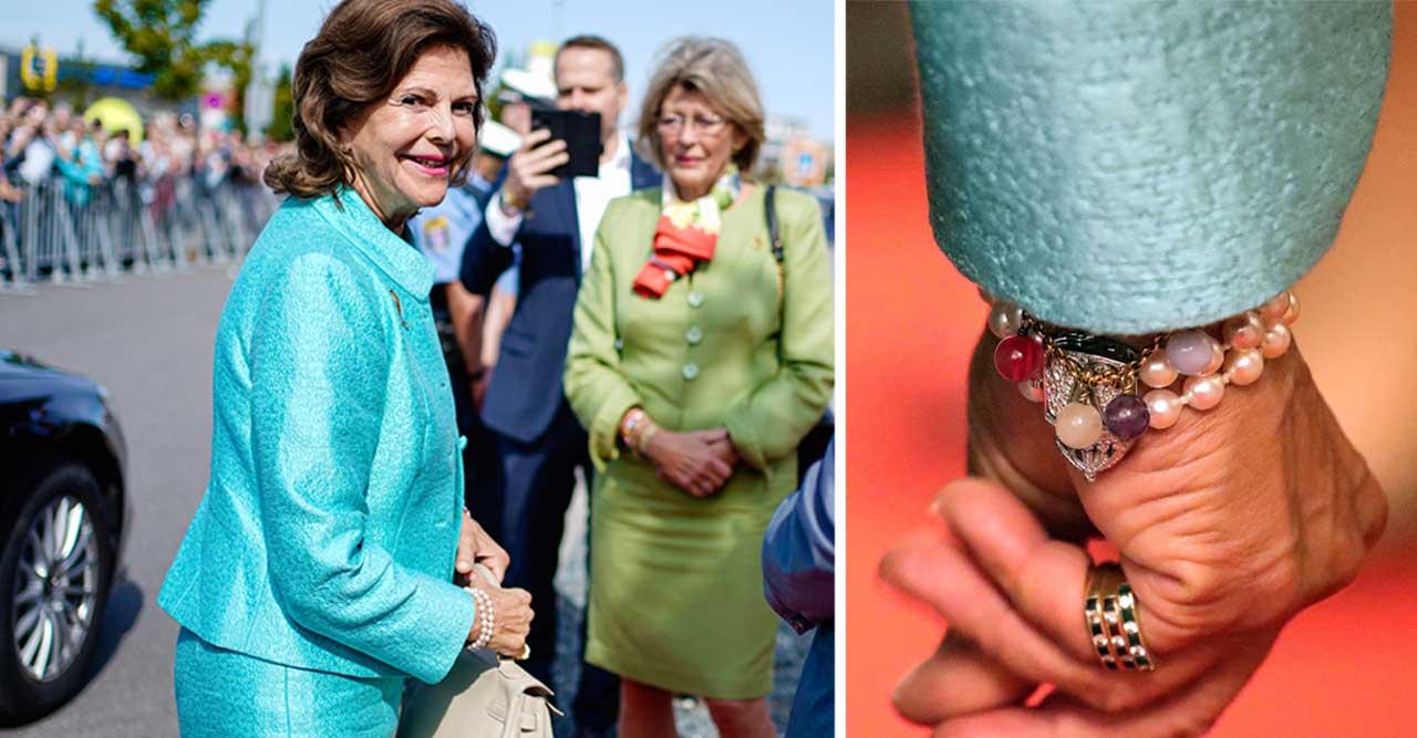 Drottning Silvia i turkos dräkt. Närbild på hennes smycken.