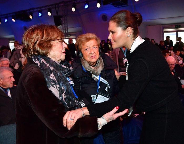 Kronprinsessan Victoria med en av de överlevande vid minneshögtiden i Auschwitz.