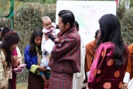 Kungen av Bhutan med baby i famnen
